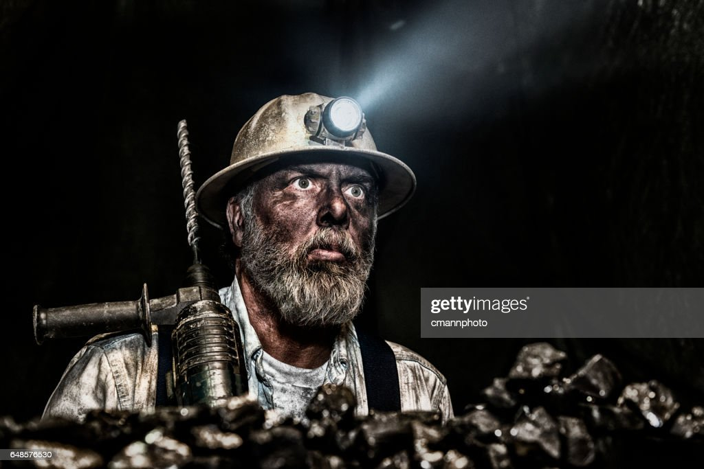 Dirty coal miner wear hardhat with a hammer drill : Stock Photo