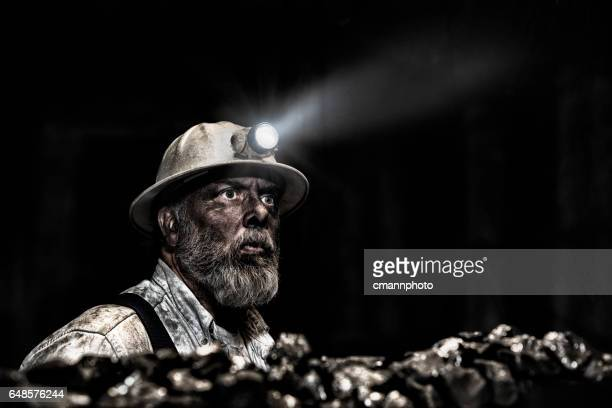 Dirty coal miner wear hardhat with light in mine
