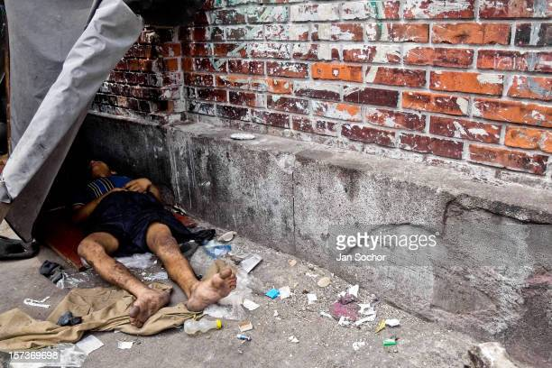 Dirty Colombian drug addict lies on the street in the slum of Calvario, Cali, Colombia, 5 April 2004. El Calvario is a slum in the pure centre of...