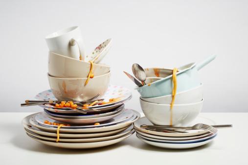 Dirty dishes pile needing washing up on white background 488222865