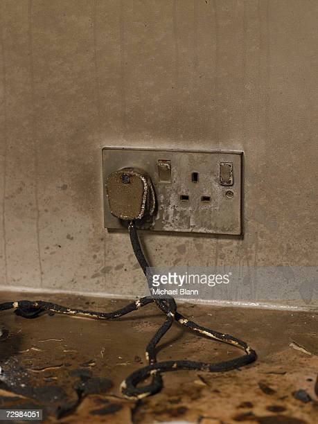 Dirty electric plug with frayed cable in dirty wall outlet
