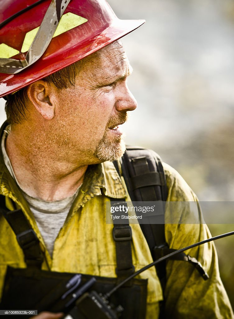 Dirty firefighter with radio, close-up : Foto stock