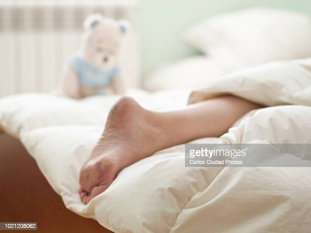 dirty foot of young woman on white bed with morning light - dirty feet stock pictures, royalty-free photos & images