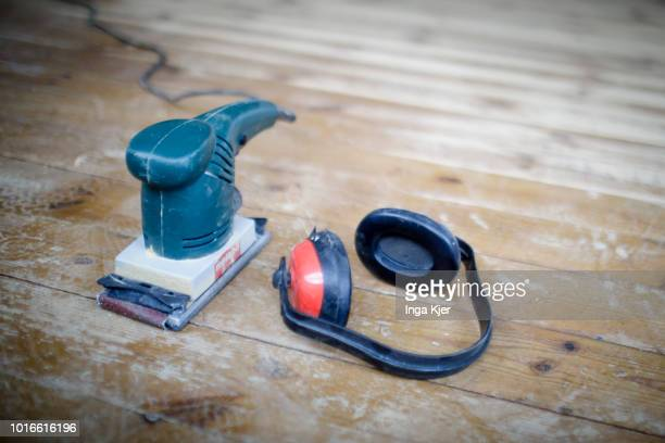 A dirty grinder and noise protection headphones are lying on a wooden floor on July 24 2018 in BERLIN GERMANY