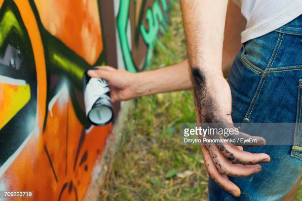 dirty hand of artist painting graffiti on wall - hands in her pants stock pictures, royalty-free photos & images