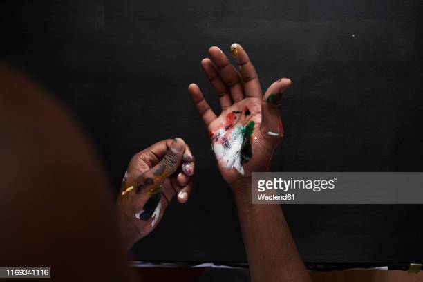dirty hands of artist with colorful paints against black background - 芸術家 ストックフォトと画像
