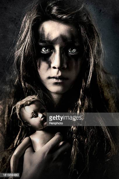 dirty little girl holding creepy doll - run down stock photos and pictures