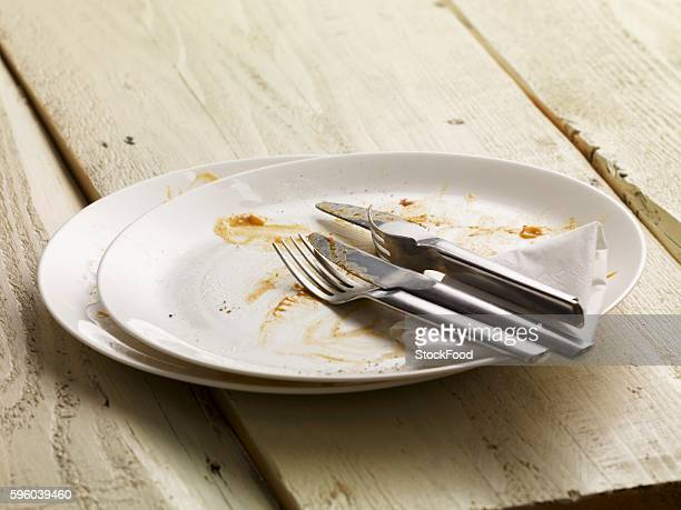 A dirty plate with cutlery and a paper napkin