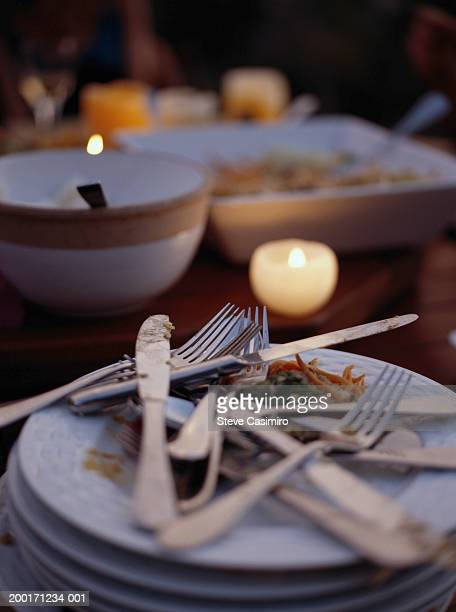 Dirty plates and cutlery on candlelit table, close-up