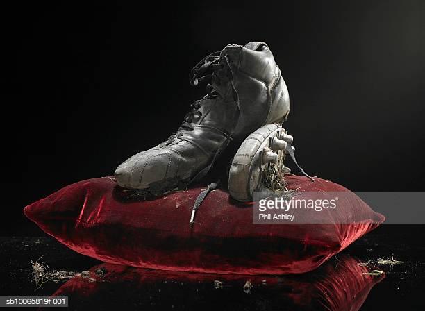 Dirty soccer shoes on velvet cushion