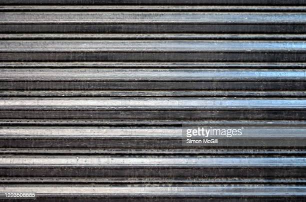 dirty stainless steel roller shutter on a shopfront - ribbed stock pictures, royalty-free photos & images