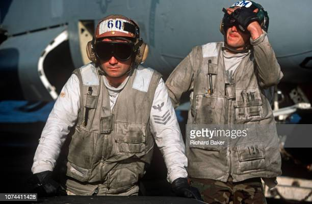 Dirty US Nacy crewmen on the deck of US Navy aircraft carrier USS Harry S Truman during its deployment patrol of the nofly zone at an unknown...