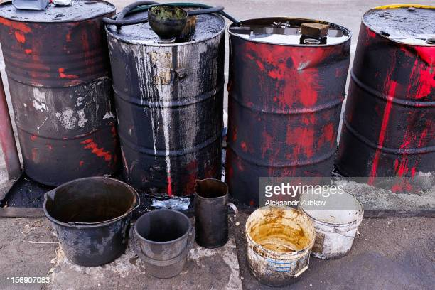 dirty used colorful oil drums are modified to look like garbage cans in the engine room. used engine oil in large barrels, buckets or containers. environmental pollution, hazardous waste disposal - drum container stock pictures, royalty-free photos & images