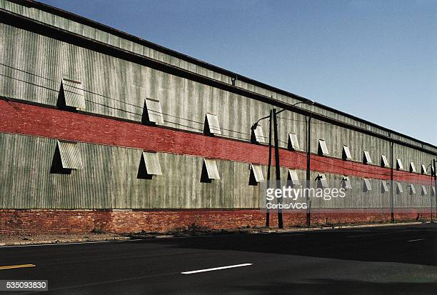 dirty warehouse sitting on road's edge - vcg stock pictures, royalty-free photos & images