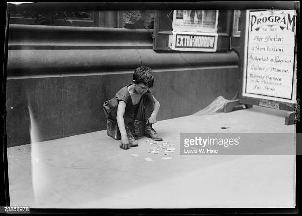 A dirty young shoeshine boy dressed in filthy clothing looks at an assortment of baseball cards as he sits on his box outside a movie theater USA...