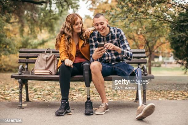couple de personnes handicapées assis sur un banc dans le parc - discrimination photos et images de collection