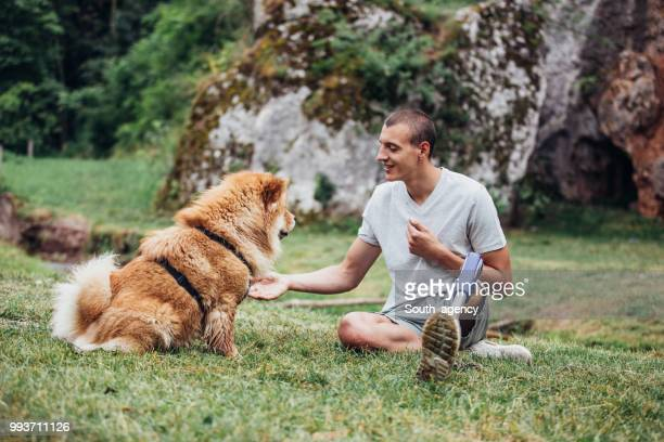 disability guy and pet relaxing - chow dog stock pictures, royalty-free photos & images