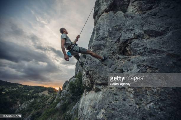 Disability man climbing high on rock mountain