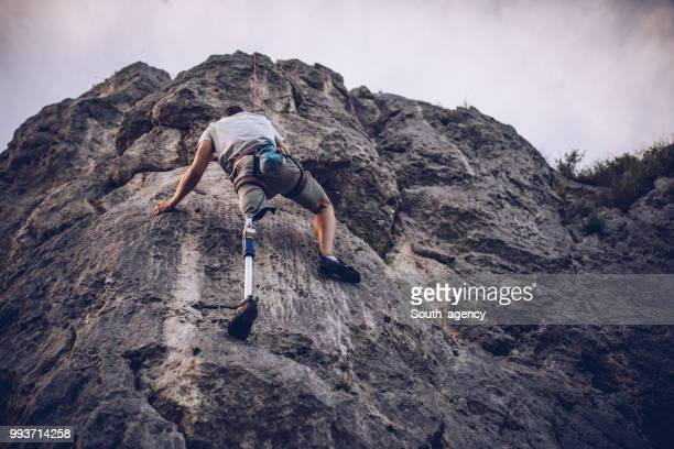 disability man climbing rocks - amputee stock pictures, royalty-free photos & images