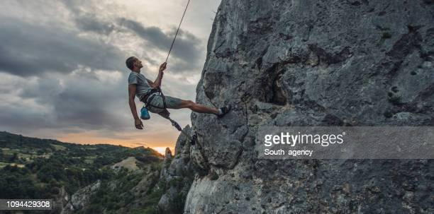 disability man free climbing on rock mountain - prosthetic equipment stock pictures, royalty-free photos & images