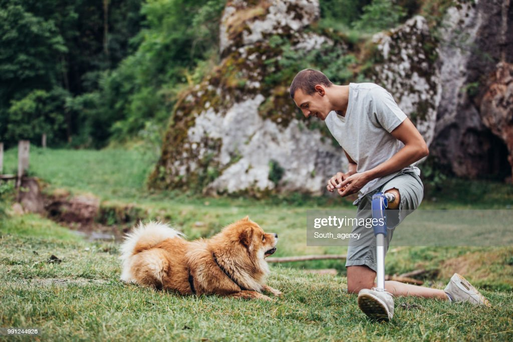 Disability man playing with pet : Stock Photo