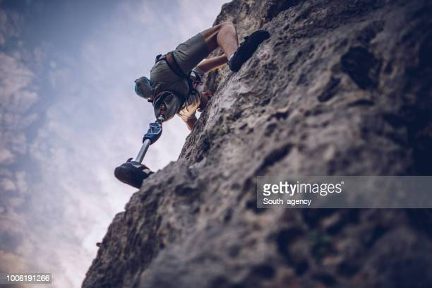 Disability man with prosthetic leg free rock climbing