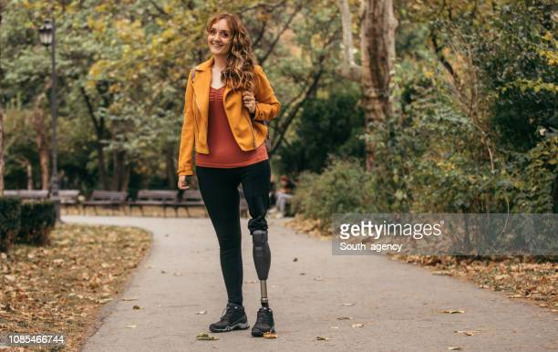 disability woman standing in park - amputee stock pictures, royalty-free photos & images