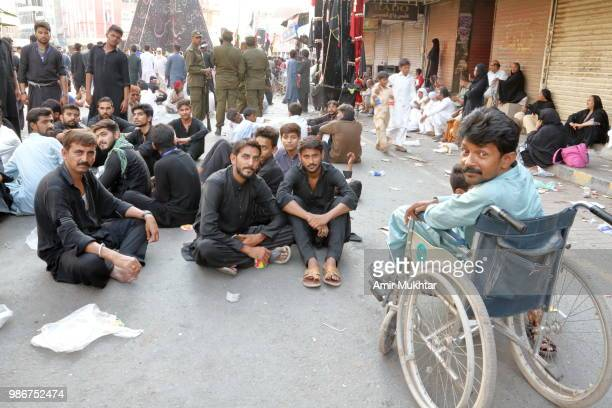 Disable and other Pakistani Shia Muslims carrying flags and resting before the self-flagellation on the main bazar of clock tower during a Muharram procession on road