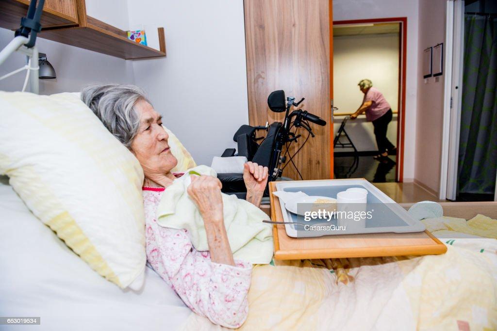 Senior vrouw ontbijten In haar Bed in het bejaardentehuis uitschakelen : Stockfoto