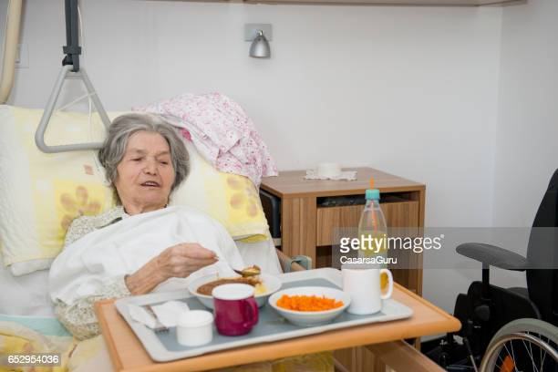 disable senior woman having lunch in her bed - residential care stock photos and pictures
