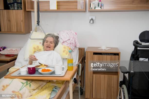 Ältere Frau mit Mittagessen In ihrem Bett zu deaktivieren