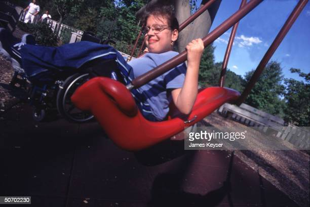 Disabled 12yearold Hannah Kristan enjoying ride on highback swing specially designed for kids confined to wheelchairs at Jonathan's Dream Hasbro Natl...