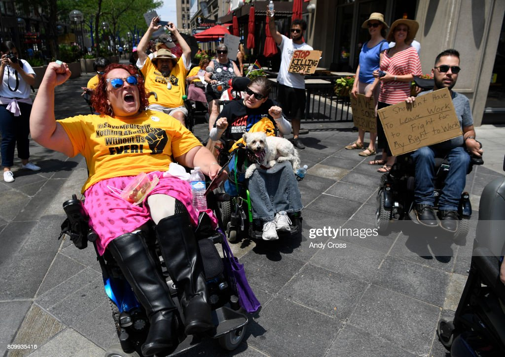 Disabled activist Sarah Metsch, left, leads fellow protesters in a chant along the 16th St. Mall after a Save Medicaid Rally at Skyline Park near U.S. Sen. Cory Gardner's Denver office July 06, 2017 in Denver. Several hundred protesters gathered to keep up the pressure on Sen. Gardner to vote no on the proposed health care bill, which would limit Medicaid to those in need. Last week ten disabled protesters were arrested including Russell, after refusing to leave Sen. Gardner's office after a sit-in protest.