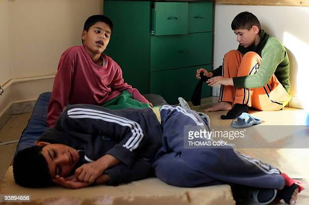 Disabled and orphaned Romanian children hang around in a room on November 24 at the Targu Jiu orphanage southwestern Romania after being transfered...