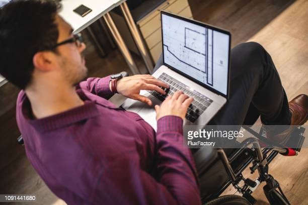 disabled architect in wheelchair typing on his laptop - assistive technology stock photos and pictures