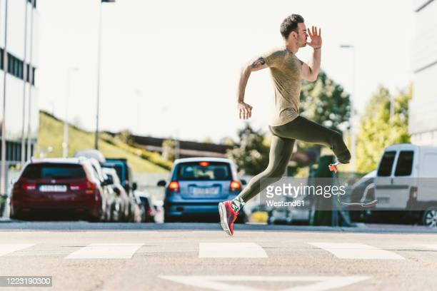 disabled athlete with leg prosthesis exercising in the city on a zebra crossing - animated zebra stock pictures, royalty-free photos & images