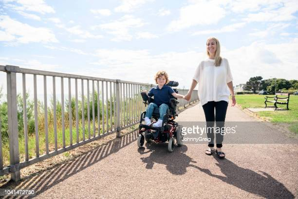 disabled boy in wheelchair holding mother's hand on path - wheelchair stock pictures, royalty-free photos & images