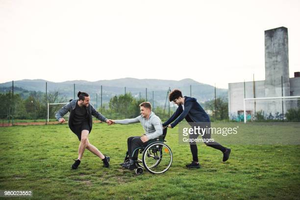 A disabled boy in wheelchair with a teenager friends outside having fun.