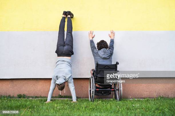 A disabled boy in wheelchair with teenager friend doing handstand on the wall. Rear view.