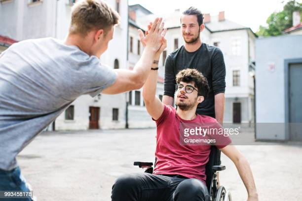 A disabled boy in wheelchair with teenager friends outside giving high five.