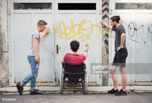 A disabled boy in wheelchair with teenager friends outside having fun.