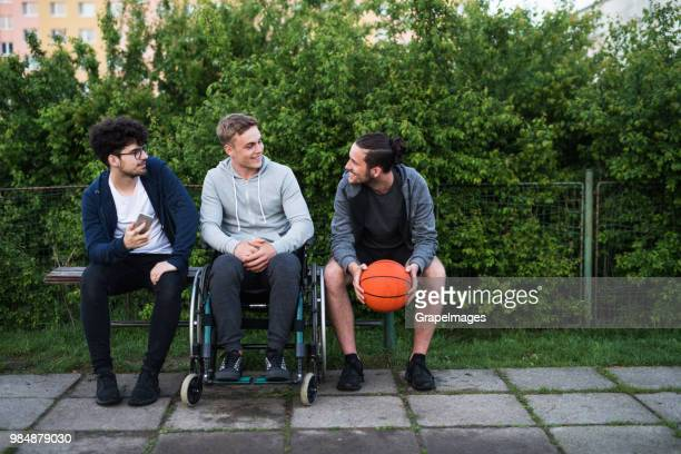A disabled boy in wheelchair with teenager friends sitting on a bench outside in town.