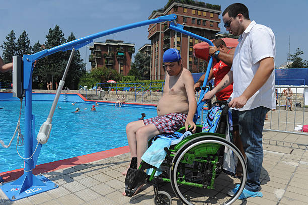 A Disabled Boy Test The Mechanical Device To Help People In Public Swimming Pool On