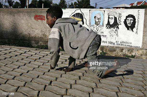 A disabled boy walks past a mural showing Argentinian revolutionary Che Guevara Jamaican singer Bob Marley and Ethiopian dictator Mengistu Haile...