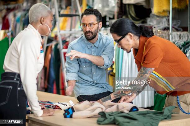 disabled businessman analyzing textile with team - disability collection stock pictures, royalty-free photos & images
