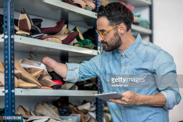 disabled businessman examining shoes at studio - disability collection stock pictures, royalty-free photos & images