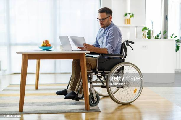 disabled businessman reading reports while working at home. - physical disability stock pictures, royalty-free photos & images