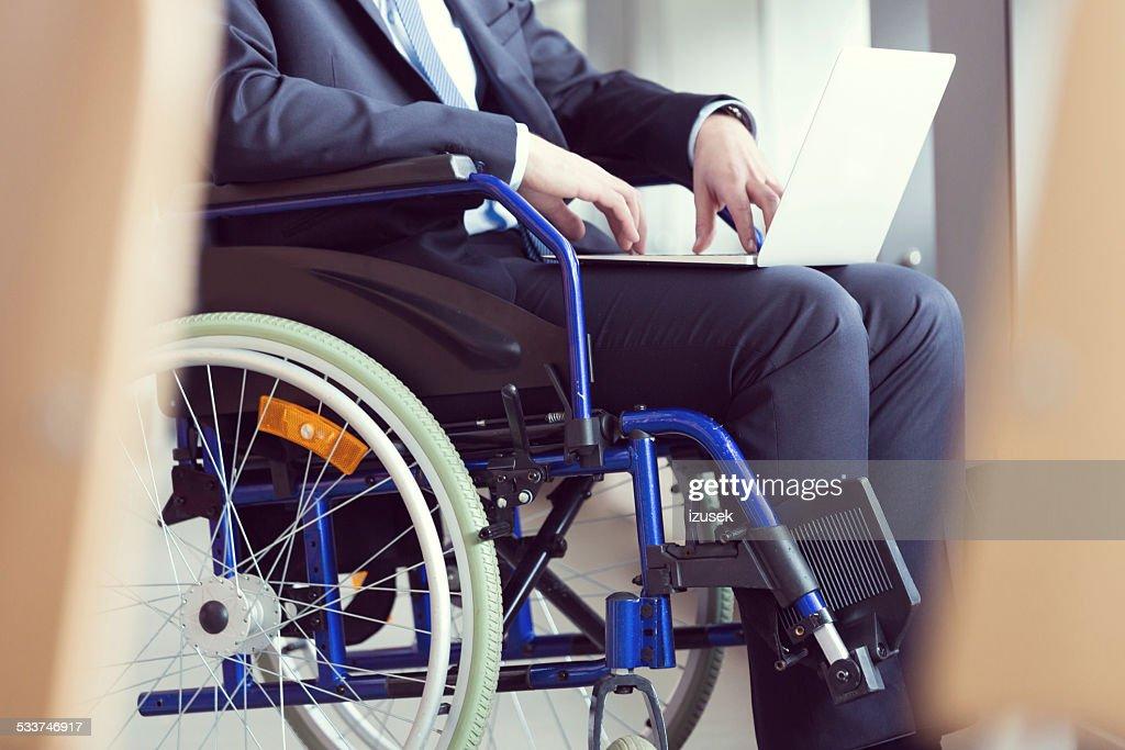 Disabili uomo d'affari seduto su una sedia a rotelle : Foto stock