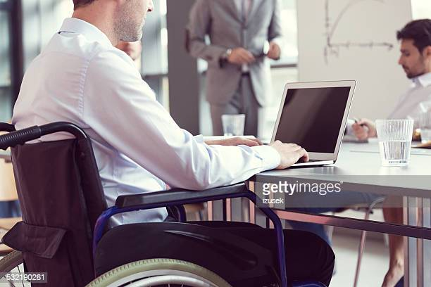 Disabled businessman working on laptop in an office