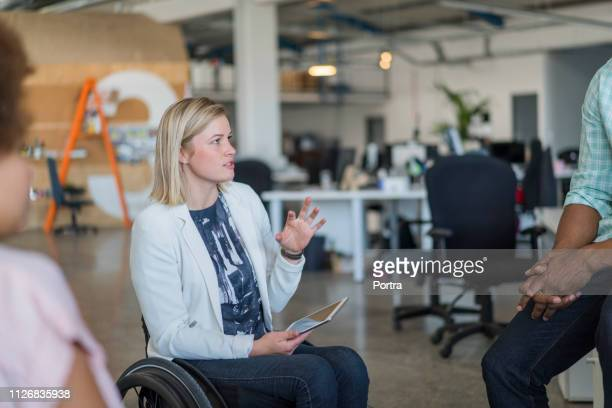disabled businesswoman discussing with colleagues - disabilitycollection stock pictures, royalty-free photos & images